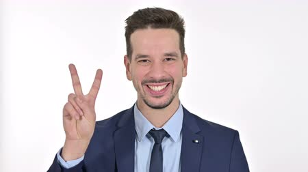 primo posto : Portrait of Successful Young Businessman showing Victory Sign , White Background Filmati Stock