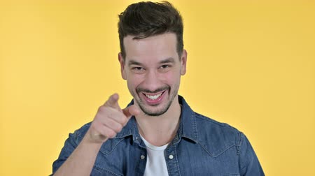 merging : Portrait of Attractive Young Man Pointing at Camera, Yellow Background