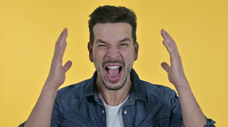gritar : Portrait of Angry Young Man Screaming, Yellow Background