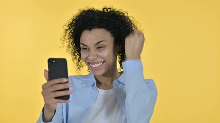 banking document : Portrait of Casual African Woman Celebrating Success on Smartphone Stock Footage