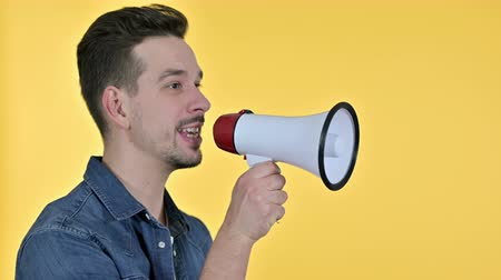 white out : Portrait of Young Man making Announcement on Loudspeaker, Yellow Background