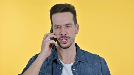 gritar : Portrait of Upset Young Man getting Angry on Smartphone, Yellow Background