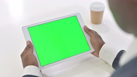 a böngésző : African Man Looking at Tablet with Chroma Key Screen Stock mozgókép