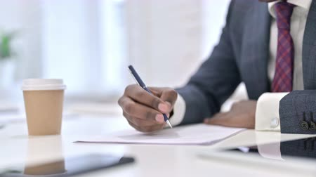 трейдер : Close up of African Businessman doing Paperwork