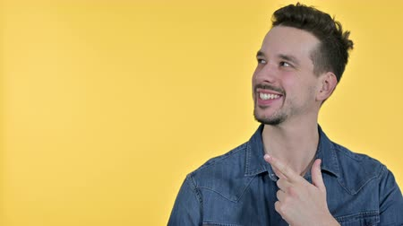 unveil : Portrait of Young Man Pointing at Product, Yellow Background