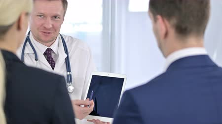 counsel : Portrait of Attractive Male Doctor Discussing Reports with Patients
