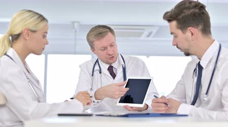 counsel : Serious Male Doctor Discussing Reports on Tablet with Team in Office Stock Footage