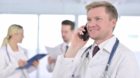 medical student : Portrait of Serious Male Doctor Talking on Smartphone