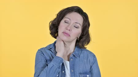 cansado : Old Woman with Neck Pain on Yellow Background Stock Footage