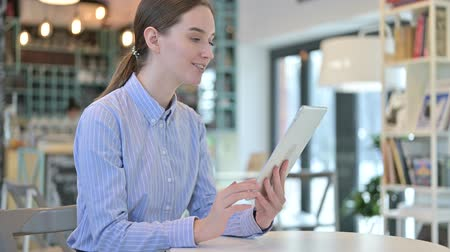 distante : Video Chat on Tablet by Young Businesswoman in Cafe Stock Footage