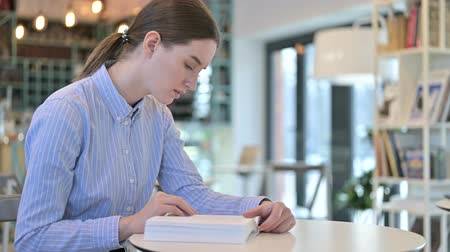 introspection : Focused Young Businesswoman Reading Book in Cafe