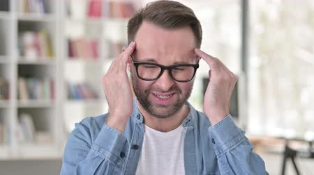 irritação : Young Man in Glasses with Headache