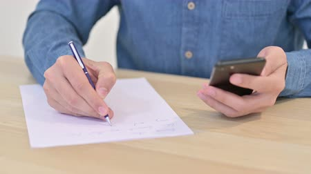 documentos : Close up of Man Writing on Paper using Smartphone Stock Footage