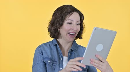 pouze ženy : Video Chat on Tablet by Old Woman, Yellow Background