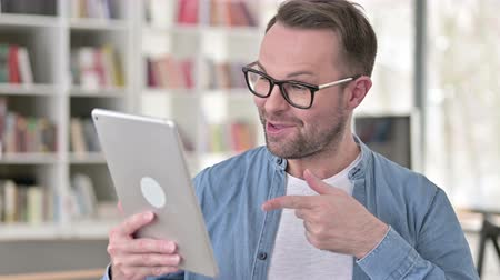 negotiate : Video Chat on Tablet by Young Man in Glasses Stock Footage