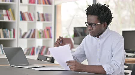 documentos : Focused African Man doing Paperwork in Office