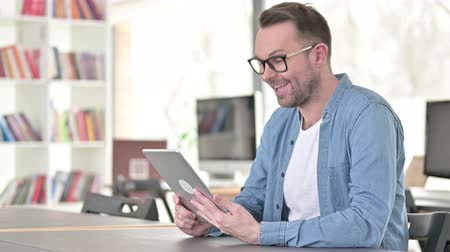 distante : Video Chat on Tablet by Young Man in Glasses Stock Footage