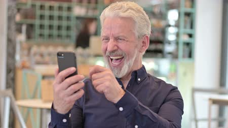 torcendo : Portrait of Old Man Celebrating on Smartphone