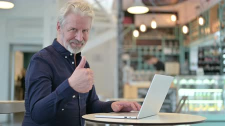 polegar : Thumbs up by Old Man with Laptop in Cafe