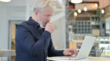 discomfort : Coughing Old Man using Laptop in Cafe Stock Footage