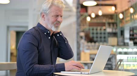 ortopedia : Laptop use by Old Man with Neck Pain in Cafe Wideo