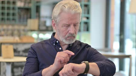 urgenza : Ritratto di Smart Watch utilizzato da Serious Old Man Filmati Stock