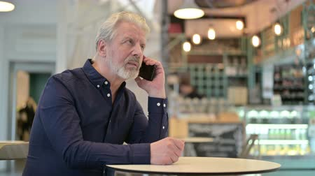 adults only : Old Man Talking on Smartphone in Cafe Stock Footage