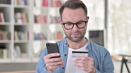 waluta : Online shopping on Smartphone by Young Man in Glasses