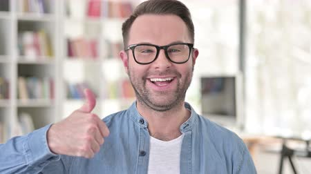 kciuk : Young Man in Glasses showing Thumbs Up