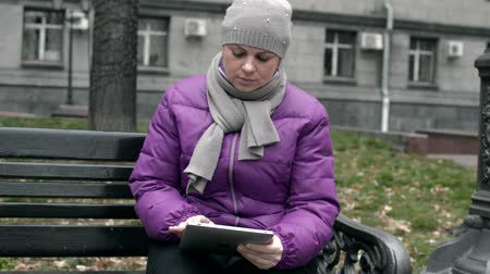 video A woman on a bench with the Tablet