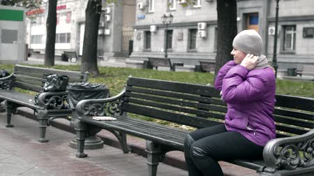 video a woman sits on a bench in the Park