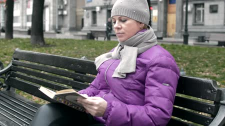video a woman sits on a bench with a book