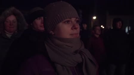 A woman looks at a concert at the crowd in winter