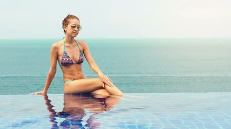 reflexão : Woman in luxury infinity swimming pool with view at blue sea