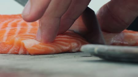 carne : Sushi Chef Slices fresh Salmon on the sushi bar. A sushi-man slicing a salmon steak. Preparing sushi. Japanese cuisine recipes.