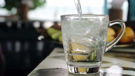 льдом : Pouring soda water with ice and bubbles in the glass on the bar