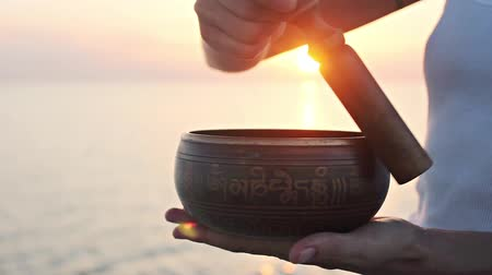 исцелять : Practice with ritual singing bowl at the beach on sunset