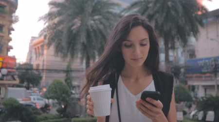 sending : Woman with smartphone and coffee walking in the city, steadicam shot Stock Footage