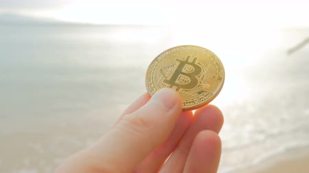 объекты : Man hands holding crypto currency BTC Bitcoin coins on the beach