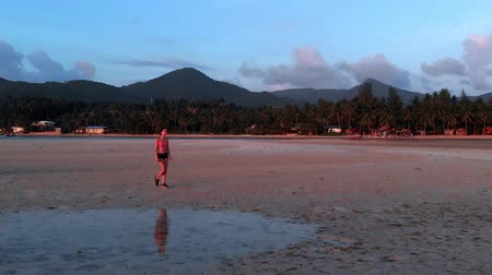 aerobic : a young woman jogging at the beach on sunset. aerial drone shot, slow motion