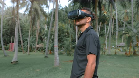 senhor : Man using virtual reality headset in the jungle Vídeos
