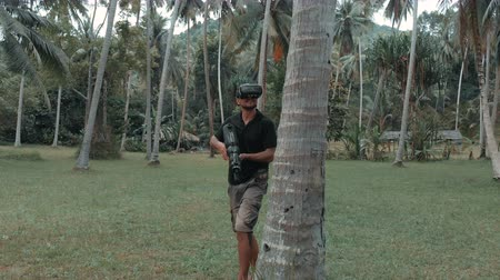 senhor : Man with weapon playing virtual reality game in the jungle, drone shot Vídeos