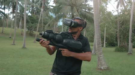 senhor : Man in virtual reality headset with weapon in the jungle running in slow motion