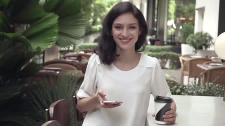 Super slow motion, young business lady with smartphone in city cafe