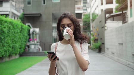 girl walking on city streets and drinking coffee to go in super slow motion Vídeos