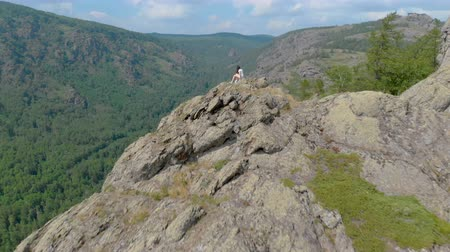 šplhání : A young woman is sitting on the edge of an impressive mountain cliff
