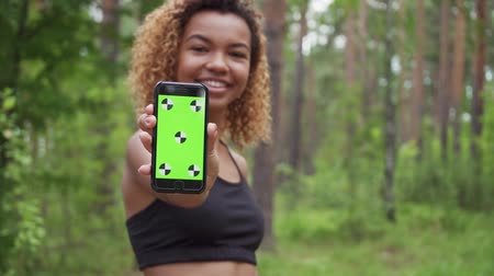 húszas évek : Black young woman using smartphone after jogging and shows green screen to the camera in slow motion