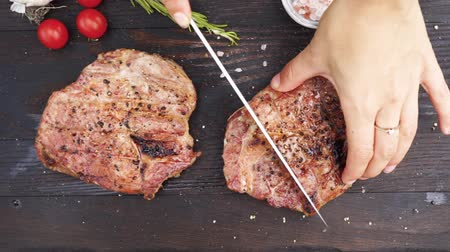 female hands cut juicy grilled steak on a wooden table