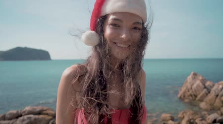 Young sexy woman near the swimming pool in Santa hat celebrating New Year and Christmas
