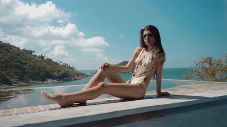 lux : dolly shot of beautiful woman resting on the edge of swimming pool on the luxury villa